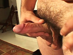 Horny beefy stud jerking his cock off on sofa for gay friend