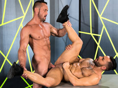 Tattooed Bruno Bernal lifts his chin to kiss towering Myles Landon. A light dusting of hair spreads across Bruno's bulging pecs, and his abs ripple as he kneels. Myles is a smooth, muscled bodybuilder; his nips are erect and his massive cock twitches wi